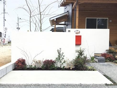 壁を背景に植木を植える
